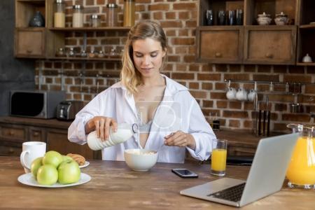 Photo pour Jeune femme blonde attrayante ayant des flocons de maïs avec du lait pour le petit déjeuner dans la cuisine - image libre de droit