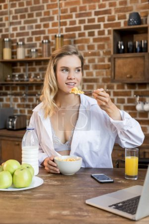 woman having breakfast in kitchen