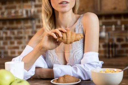 Photo for Cropped image of young blonde woman having croissant for breakfast in kitchen - Royalty Free Image