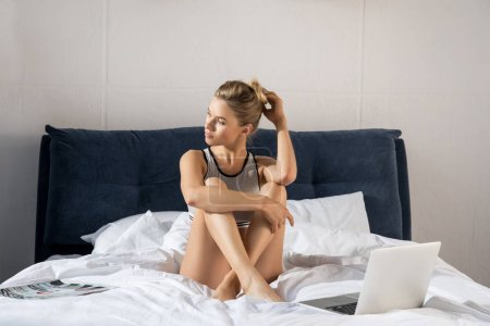 Photo for Young attractive woman sitting on bed with laptop in bedroom - Royalty Free Image