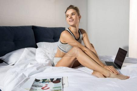 woman with laptop in bedroom