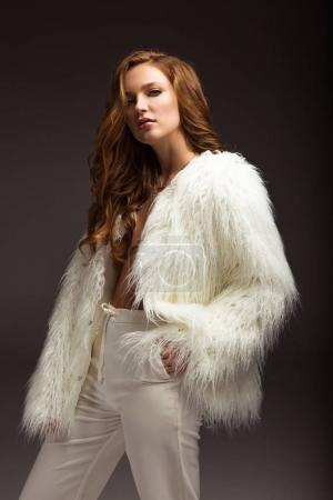 Photo pour Femme posant en costume blanc et regardant la caméra isolée sur gris - image libre de droit