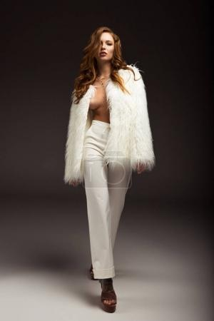 sexy woman walking in unbuttoned white fluffy jacket