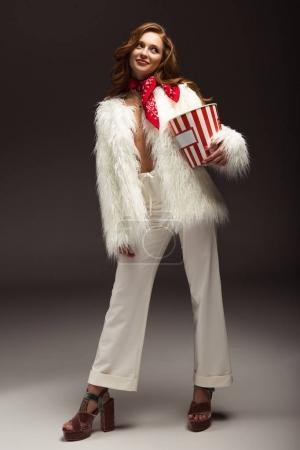 Photo pour Femme souriante debout avec boîte de maïs soufflé et regardant loin - image libre de droit