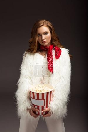 Photo pour Femme sérieuse en tenue élégante debout avec boîte de maïs soufflé isolé sur gris - image libre de droit