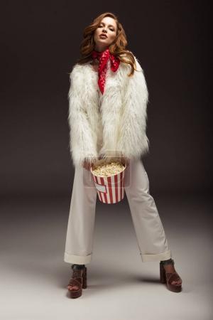 Photo pour Femme séduisante en tenue élégante posant avec boîte de pop-corn - image libre de droit