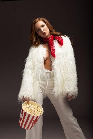 Photo pour Femme aux cheveux bruns tenant du pop-corn à la main isolé sur gris - image libre de droit