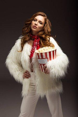 Photo pour Style fille debout avec boîte de pop-corn et regardant la caméra - image libre de droit