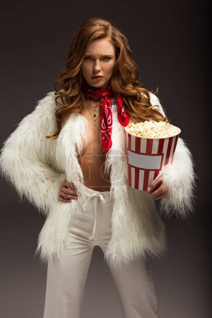 Photo pour Femme sérieuse en tenue blanche debout avec boîte de maïs soufflé - image libre de droit