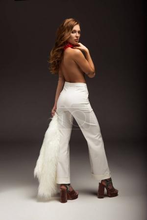 Photo pour Femme sexy avec dos nu en pantalon blanc regardant par-dessus l'épaule - image libre de droit