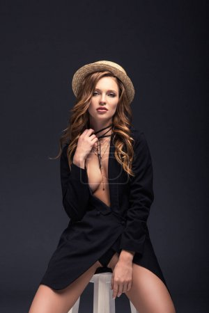 sexy woman in straw hat touching necklace isolated on gray