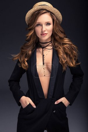sexy woman standing in straw hat and hands in pockets isolated on gray