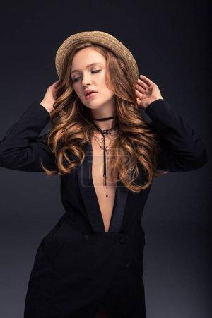 Photo pour Femme sexy posant en veste noire et chapeau de paille isolé sur gris - image libre de droit