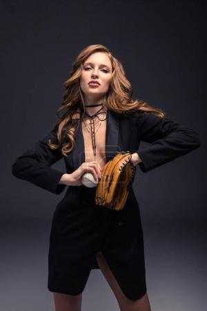 seductive woman in black jacket and curly hair posing with baseball mitt and ball
