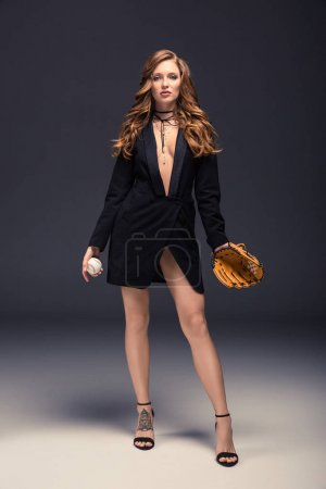 seductive woman in black jacket and curly hair holding baseball mitt and ball