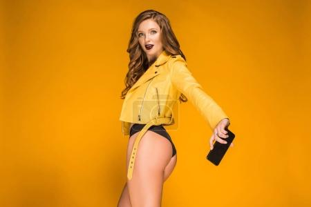 sexy girl taking selfie with smartphone from bottom and looking at camera