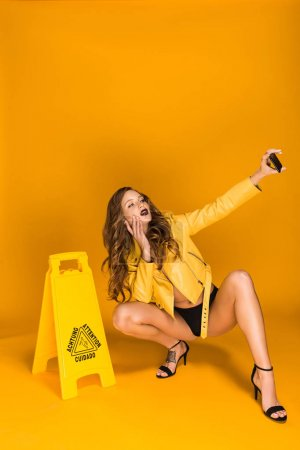 sexy woman squatting and taking selfie with wet floor sign