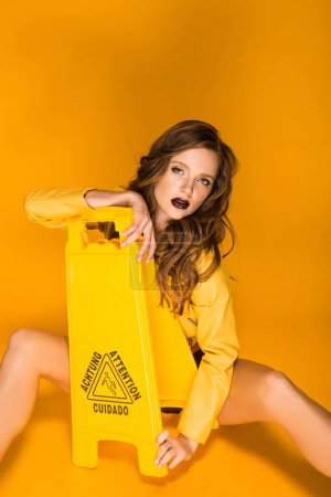 sexy girl sitting and leaning on wet floor sign