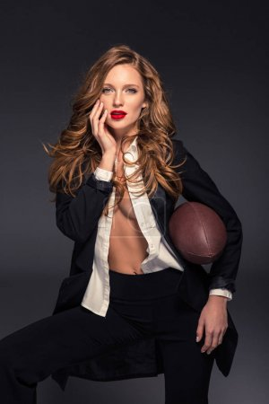 seductive woman touching face with hand and holding american football ball isolated on gray