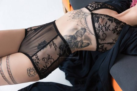 cropped image of seductive tattoed girl in transparent lingerie posing on couch