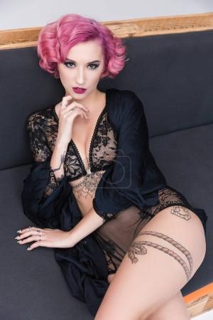 seductive tattoed pink haired girl in transparent lingerie posing on couch