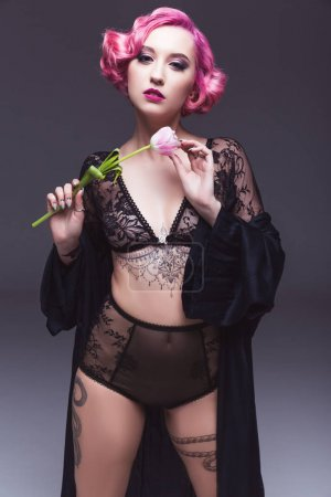 seductive tattoed pin up girl in transparent lingerie with flower infront of grey background