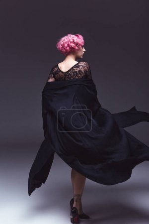 Photo for Back view of pin up girl in cloak infront of grey background - Royalty Free Image