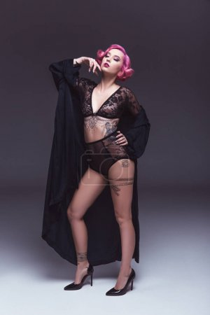 beautiful tattoed pin up girl in transparent lingerie infront of grey background