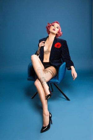 Photo pour Sexy tatoué pin up fille en veste avec boutonnière posant sur fauteuil infront de fond bleu - image libre de droit