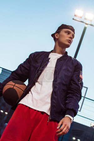 Modern player. Handsome young man in sportswear holding basketball and looking away while standing on basketball court