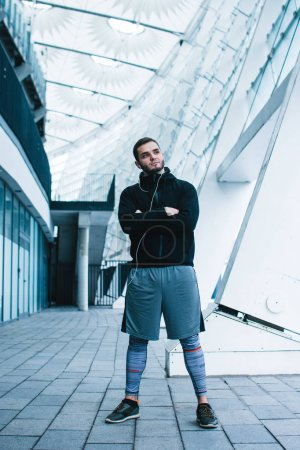 Confidant and healthy. Full length of young man in sportswear standing against industrial city view