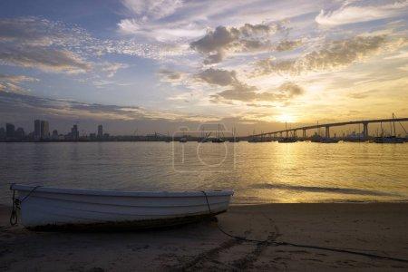 golden sunlight illuminates dinghies beached on sandy Coronado Island shore