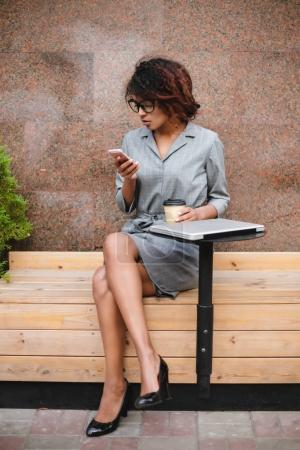 Pretty African American girl in glasses sitting on bench and using her cellphone with coffee in hand