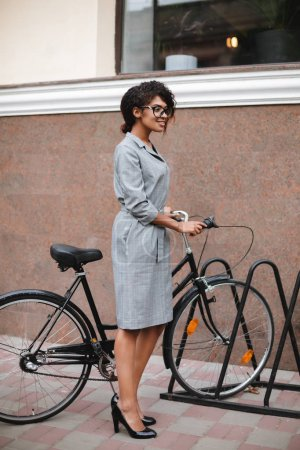Portrait of smiling African American girl in glasses standing with bicycle and happily looking aside. Young beautiful lady with dark curly hair in gray dress standing with bicycle on street