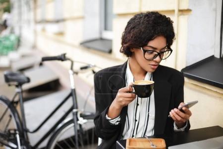 Photo pour Portrait de fille afro-américaine dans des verres assis à la table du café avec téléphone portable et tasse de café dans les mains. Belle dame aux cheveux bouclés foncés buvant du café avec vélo sur fond - image libre de droit