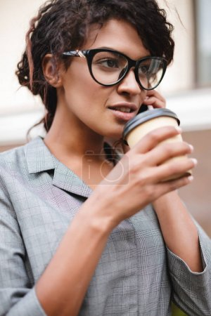 Portrait of African American girl in glasses standing and talking on her cellphone with coffee in hands