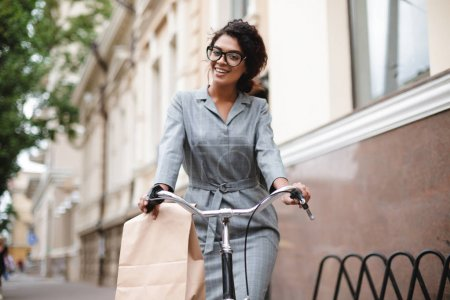 Portrait of smiling African American girl in glasses riding on bicycle and happily looking in camera