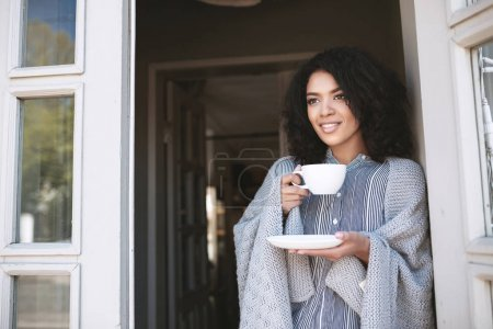 Young African American girl with dark curly hair drinking coffee leaning on door. Beautiful lady standing with cup in hand wrapped in plaid