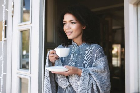 Portrait of beautiful lady wrapped in plaid with cup of coffee in hands. Cute African American girl drinking coffee in restaurant
