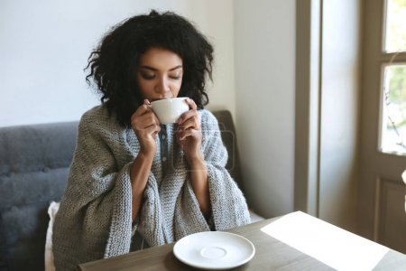 Beautiful African American girl drinking coffee in restaurant. Portrait of young lady with dark curly hair dreamily closing her eyes with cup in hands