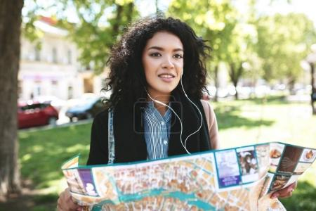 Young girl in earphones thoughtfully looking aside with map in hands on street