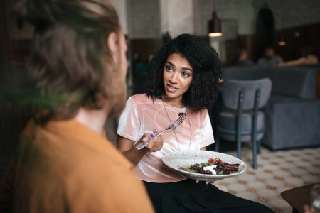 Smiling African American lady sitting at cafe with plate of salad in hand. Young girl with dark curly hair talking with friend