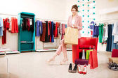 Photo of pretty girl with brown hair in pink pantsuit sitting on red chair while dreamily looking aside with shopping bag in hands in fashion boutique