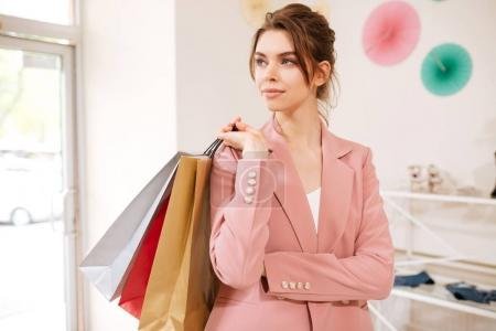 Portrait of thoughtful girl in pink jacket looking aside with colorful shopping bags on her shoulder in clothing store