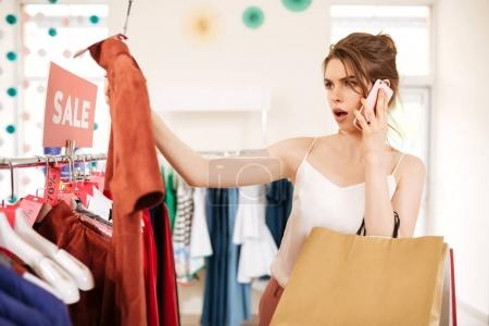 Young girl in white top standing near sale clothes rack with T-shirt in hand and amazedly looking on it in boutique