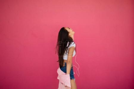 Photo for Portrait of beautiful happy girl with dark long hair standing and listening music in earphones on pink background isolated - Royalty Free Image
