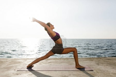 Beautiful woman standing and training yoga poses by the sea. Pretty lady in sporty top and shorts practicing yoga with sea view on background
