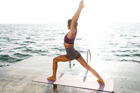 Cute woman with dark short hair standing and pulling her hands up while training yoga poses by the sea. Beautiful lady in sporty top and shorts practicing yoga with amazing sea view on background