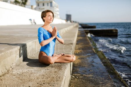 Beautiful woman sitting in lotus pose and dreamily closing her eyes while meditating by the sea. Portrait of pretty lady with dark short hair in blue swimsuit practicing yoga with sea view