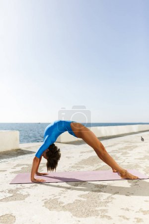 Beautiful woman with dark short hair in blue swimsuit doing yoga while standing on bridge pose with sea view on background